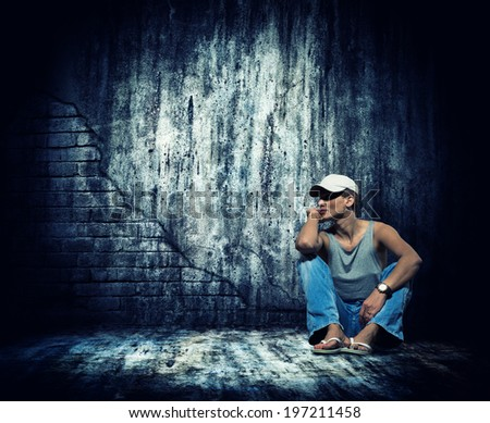 Woman sitting by the concrete grunge wall