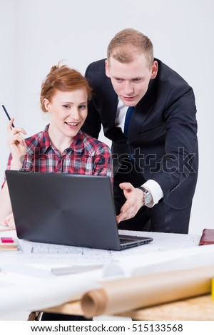 Woman sitting close to the drafting board in front of the laptop with the man leaning on the laptop screen