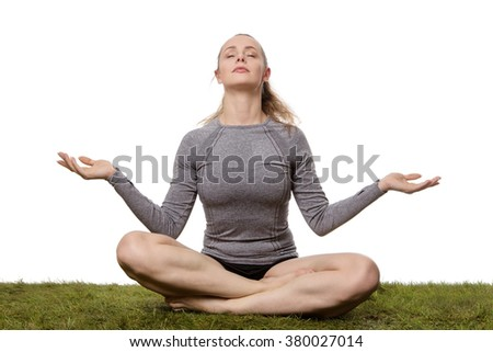 woman sitting cross legged on grass relaxing and doing yoga shot in the studio - stock photo
