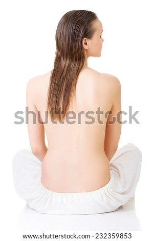 Woman sitting cross-legged wrapped in towel.