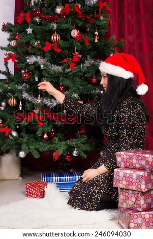 Woman sitting down  and decorates Christmas tree - stock photo