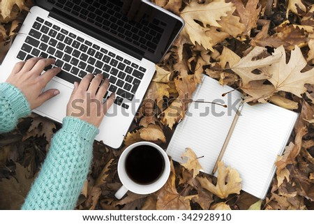 Woman sitting down in autumn leaves, using Laptop, top view