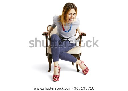 Woman sitting down on a old school chair and laughing  - stock photo