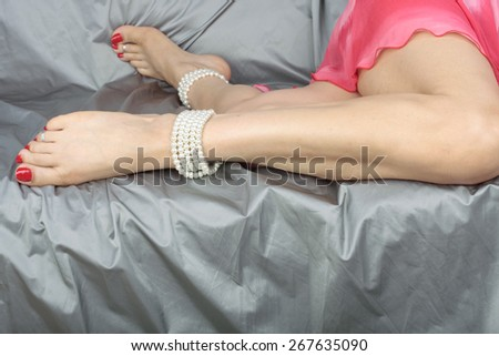 Woman sitting down with pink dress and pearls over grey - stock photo