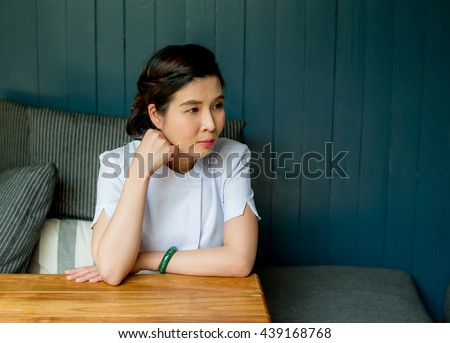 Woman sitting his hand on chin, Woman sits vacant,she stay in coffee shop, Women sit still and waiting something on sofa - stock photo