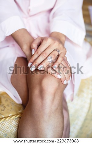 Woman sitting holding hands with ring on knees - stock photo
