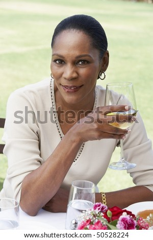 Woman sitting holding wine glass, outdoors
