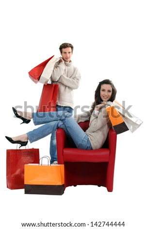Woman sitting in a chair and surrounded by shopping bags - stock photo