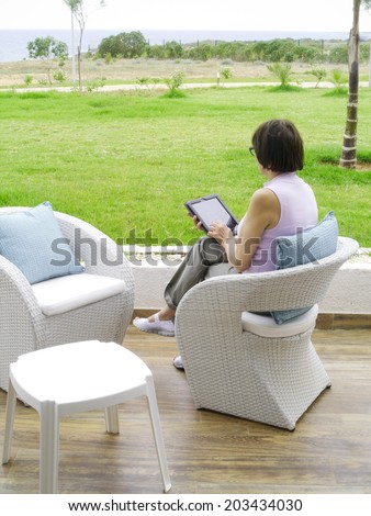 Woman sitting in a chair using tablet pc  - stock photo