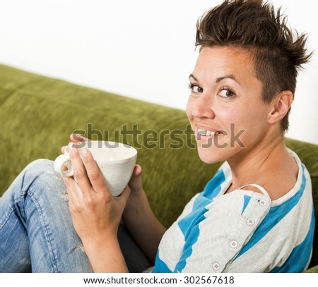 Woman sitting in a couch holding a cup of coffee or tea in her hands. - stock photo