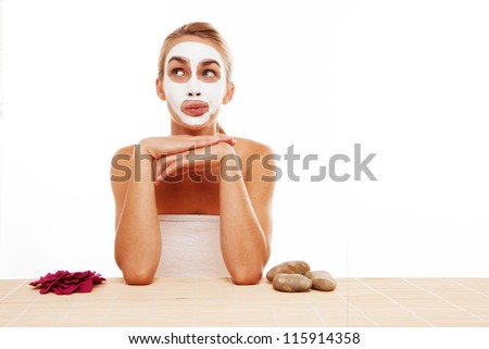 Woman sitting in a face mask at a table in a spa flanked by rose petals and hot rocks for use in beauty treatments - stock photo