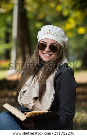 Woman Sitting In A Park And Reading Book