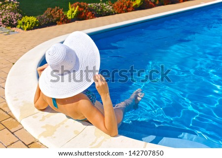 Woman sitting in a swimming pool in a large sunhat - stock photo
