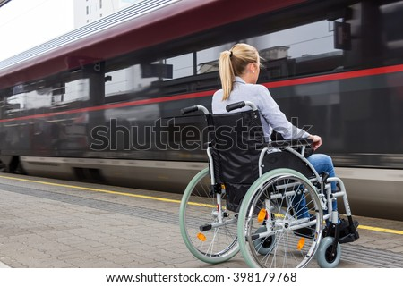woman sitting in a wheelchair at a train station - stock photo