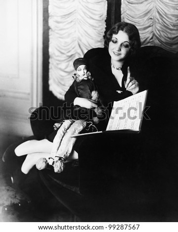 Woman sitting in an armchair with her puppet reading a book