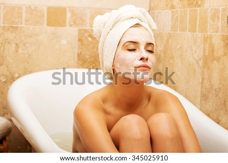 Woman sitting in bath with face mask, wearing towel on head. - stock photo