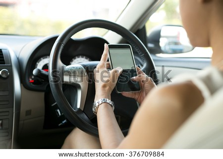 Woman sitting in car use mobile phone texting while driving dangerous - stock photo