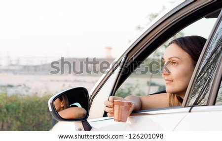 Woman sitting in car with her arm through the open window and a plastic cup with a drink in her hand - stock photo