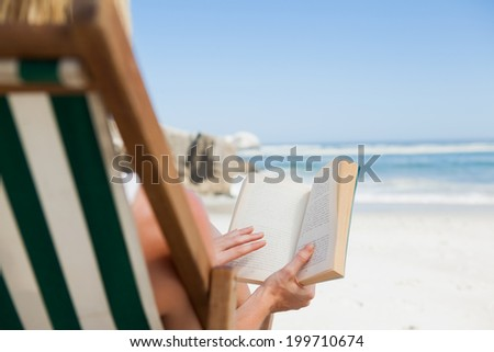 Woman sitting in deck chair at the beach reading on a sunny day - stock photo
