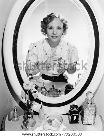 Woman sitting in front of her vanity looking into the mirror