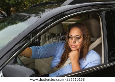 Woman sitting in her car daydreaming. - stock photo