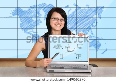 woman sitting in office and pointing to computer network - stock photo