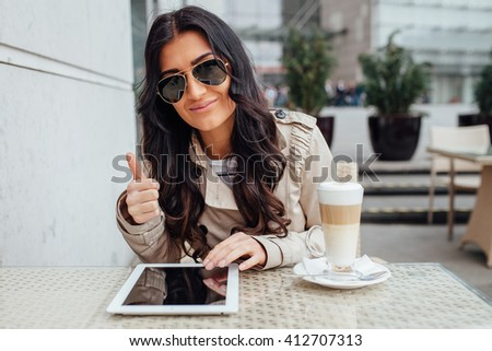 Woman sitting in outside the cafe with coffee and tablet pc. Positive emotions