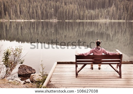 Woman Sitting in Solitude by Calm Lake - stock photo