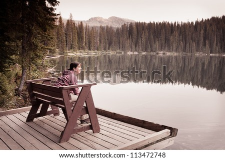 Woman Sitting in Solitude by Lake - stock photo