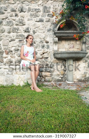 Woman sitting in the backyard reading a book