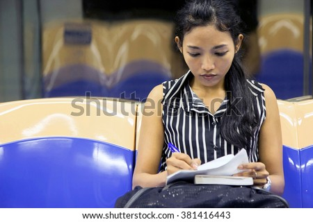 woman sitting in the subway car and writes notes. Passenger in the subway reading the notes. Passengers woman sitting in the wagon. Commuters woman studying his notes when she ride in the train.