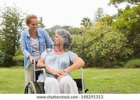 Woman sitting in wheelchair with her daughter in park on sunny day