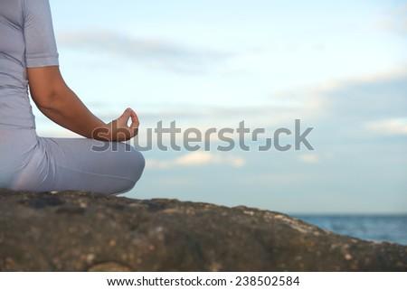 Woman sitting in yoga lotus pose ocean background - stock photo