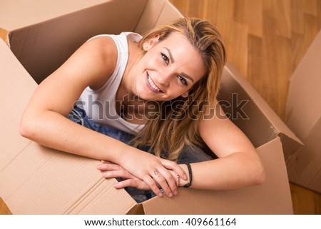 Woman sitting inside a cardboard box while packing - stock photo