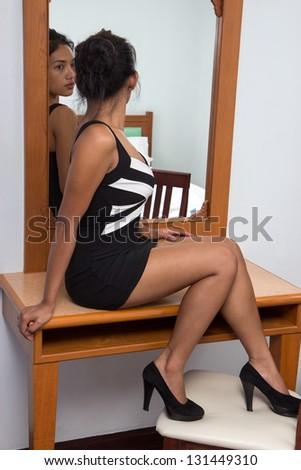 woman sitting near a mirror - stock photo