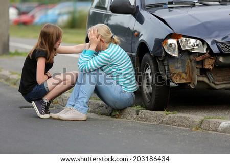 Woman sitting near the car after accident with her daughter - stock photo