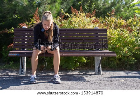 Woman sitting on a bench with smart phone - stock photo