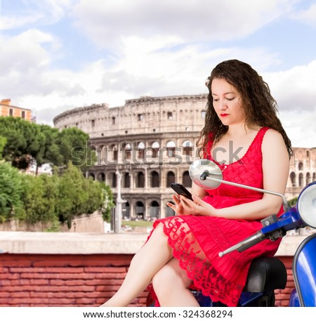 woman sitting on a blue scooter looking her mobile phone at rome with the coloseum on the background - stock photo