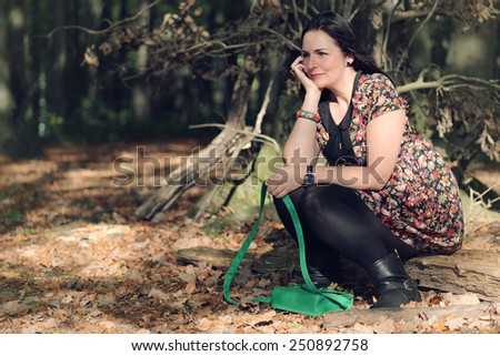 woman sitting on a branch in a forrest, vintage filter effect added - stock photo