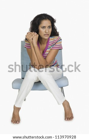 Woman sitting on a chair and looking worried - stock photo