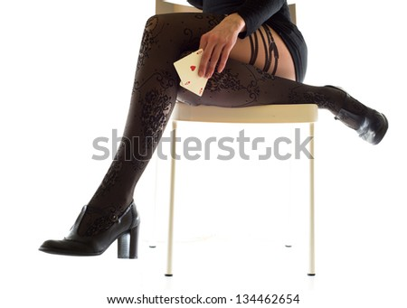 woman sitting on a chair with aces in her hand - stock photo