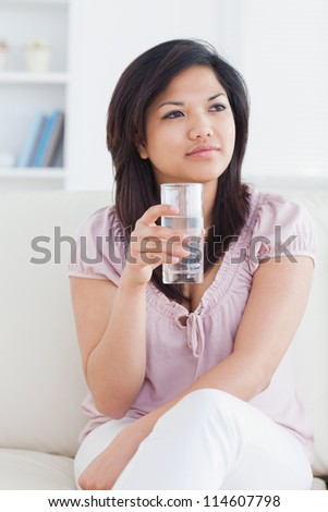 Woman sitting on a couch while crossing her legs and holding a glass of water in a living room - stock photo