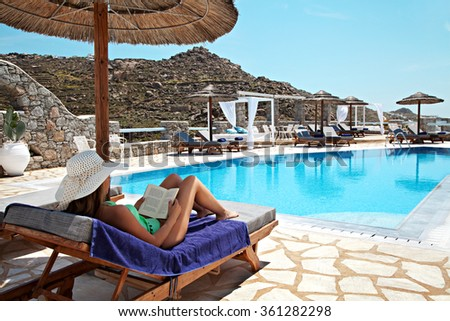 woman sitting on a deck chair and reading her book on a swimming pool - stock photo