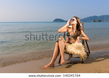 Woman sitting on a deck chair on a tropical beach - stock photo
