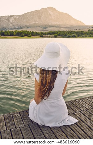 woman sitting on a dock with a white dress and hat