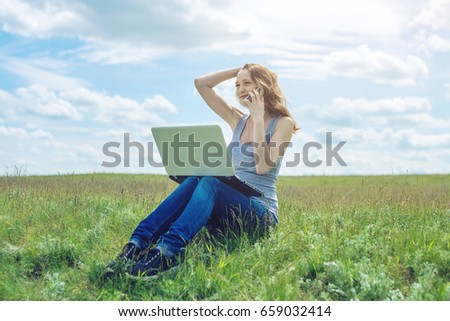 Woman sitting on a green meadow on the background of sky with clouds and working or studying with laptop wireless. The concept of nature and education