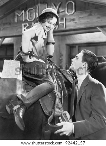 Woman sitting on a horse talking and flirting with a young man