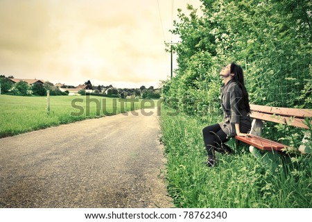 Woman sitting on a park bench near a countryside road