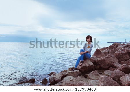 Woman sitting on a rock by the sea