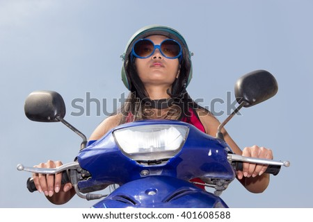 Woman sitting on a scooter on a blue background. Motorcyclist in old helmet riding motorbike on a blue background. Biker riding a motorcycle. Asian girl riding a scooter. Motorcyclist in front look.